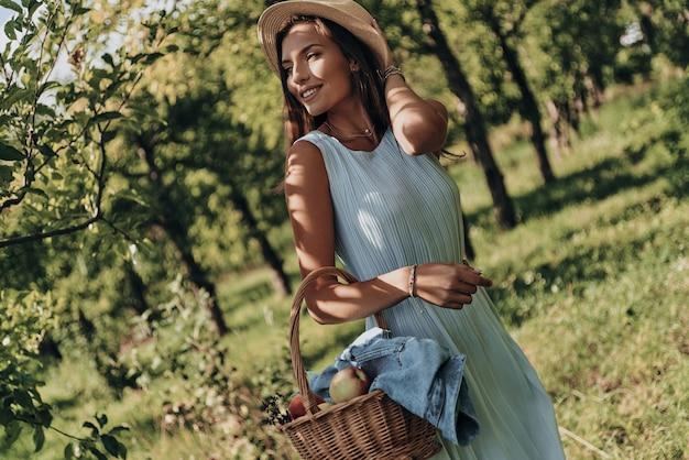 Brilhando com beleza natural. mulher jovem e atraente carregando uma cesta com maçãs e olhando para longe com um sorriso em pé no jardim