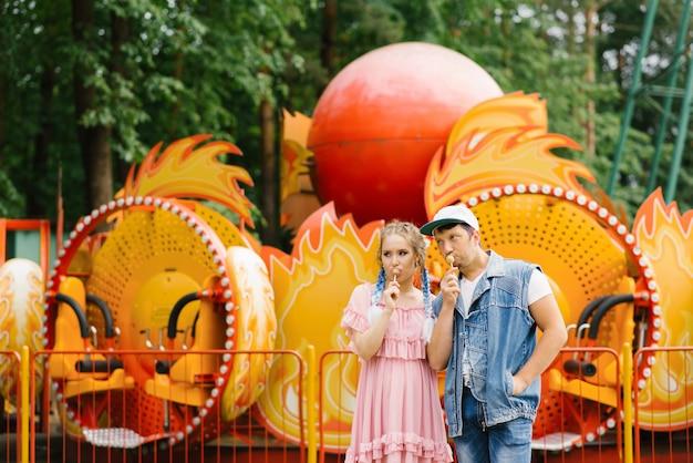 Brilhante alegre casal apaixonado, descansando em um parque de diversões. cara engraçado e garota comendo pirulitos no palito