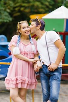 Brilhante alegre casal apaixonado, descansando em um parque de diversões.