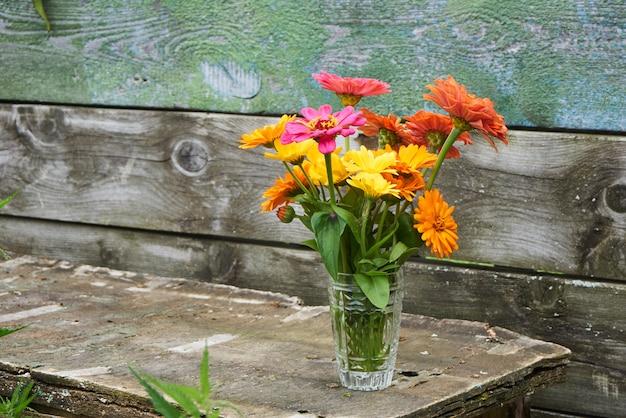 Brilhante buquê de flores em um copo em uma mesa de madeira