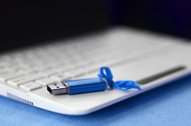 Brilhante cartão de memória flash usb azul com um laço azul encontra-se em um cobertor de tecido de lã