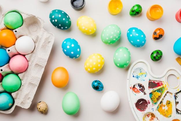 Brilhante coleção de ovos coloridos perto de recipiente, cores de água e paleta