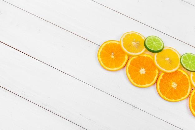 Brilhante composição de frutas cítricas em fundo branco de madeira