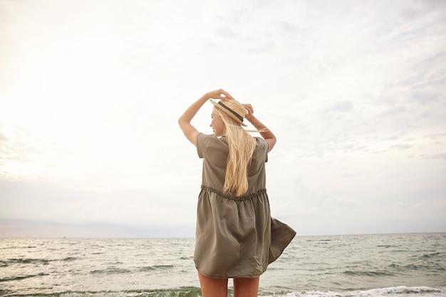Brilhante foto ao ar livre de uma jovem mulher com a cabeça esguia segurando o chapéu de palha com as mãos levantadas enquanto aprecia a vista para o mar, usando um vestido verde romântico sobre o fundo da praia