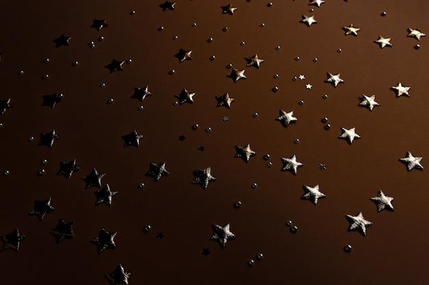 Brilhantes e estrelas dourados em um fundo escuro festivo confete com elementos de luxo glitter na vista superior