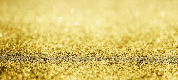 Brilho abstrato de glitter dourado desfocado com bokeh