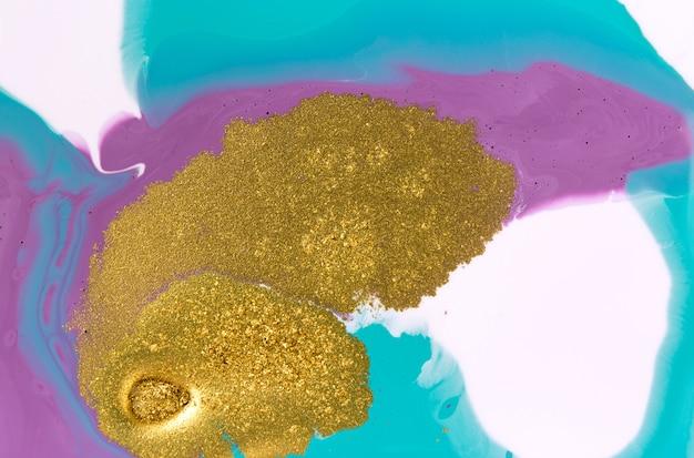 Brilho dourado sobre fundo acrílico líquido, mármore azul e roxo abstrato