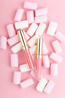Brilho labial rosa pastel sobre um fundo de doces.