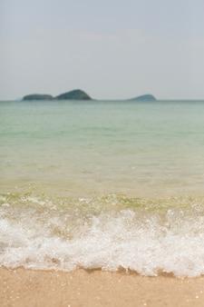 Brilho na onda fundo de areia amarela do oceano espuma do mar e onda passando pela costa