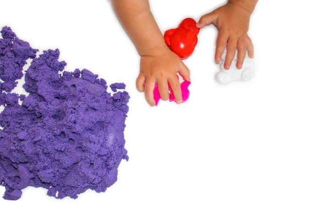 Brincadeira de criança com cinética com moldes para areia cinética em fundo branco isolado