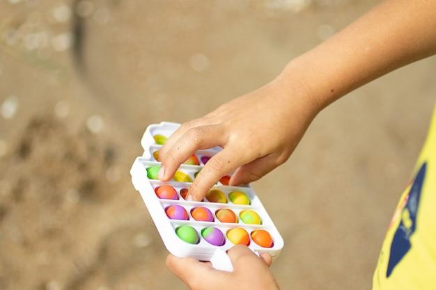 Brincadeira de criança com novo brinquedo de silicone pop na praia covinha simples em moldura de plástico