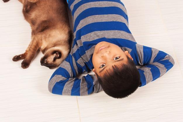 Brincadeira de menino bonito com gato marrom