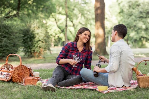 Brincalhão casal deitado sobre um cobertor com taças de vinho