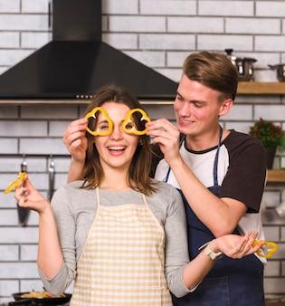 Brincalhão casal fazendo óculos de fatias de pimenta