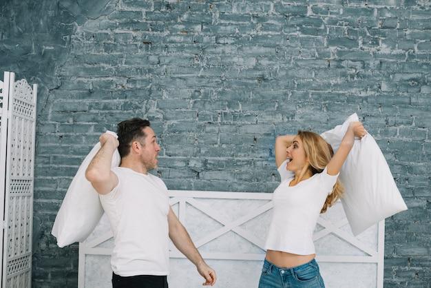 Brincalhão casal tendo travesseiro lutar em casa