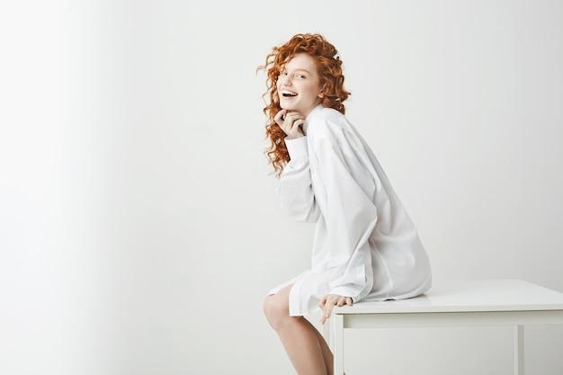 Brincalhão concurso mulher com cabelo ruivo cacheado rindo posando sentado na mesa. copie o espaço.