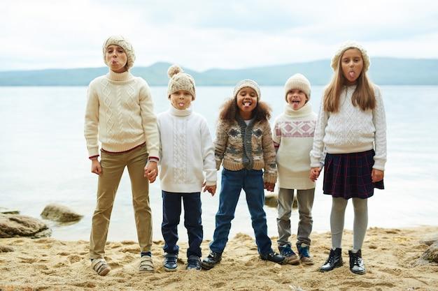 Brincalhão crianças posando pelo lago