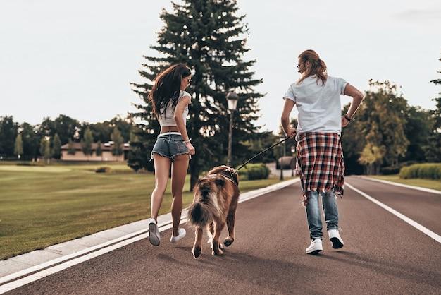 Brincalhão e cheio de amor. retrovisor de corpo inteiro de um lindo casal correndo com seu cachorro enquanto passa o tempo ao ar livre