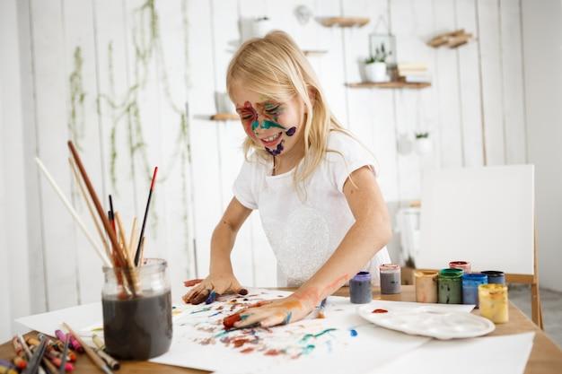 Brincalhão, linda garota loira se divertindo desenhando com as mãos, bipando as palmas das mãos em cores diferentes e colocando-as em uma folha de papel branca.