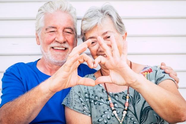 Brincalhão lindo alegre caucasiano adulto sênior casal curtindo estilo de vida toghetner com sorriso e riso fazendo o coração com as mãos. conceito de amor e parceria para sempre para pessoas felizes