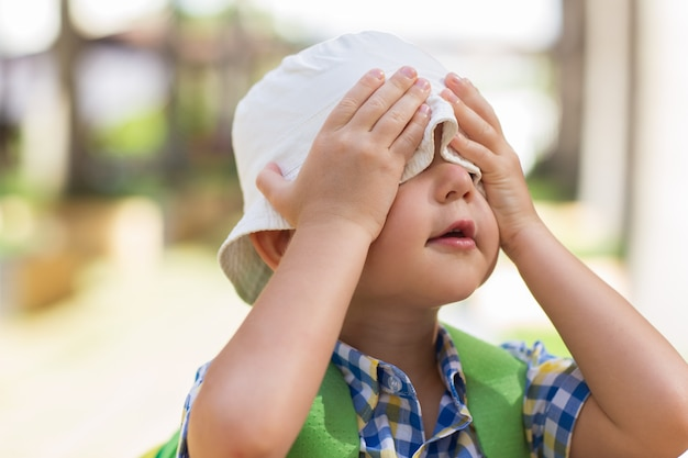Brincalhão little boy cobrindo olhos com mãos