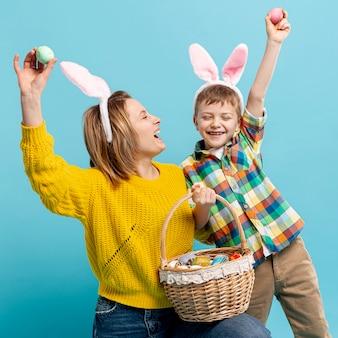 Brincalhão mãe e filho mostrando ovos pintados