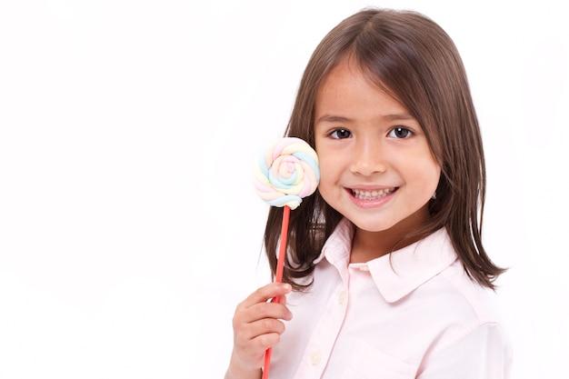 Brincalhão menina bonitinha posando com marshmallow de cor pastel doce