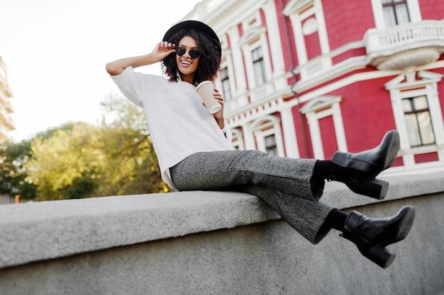 Brincalhão mulher negra com cabelos afro, sentado na ponte e se divertindo. vestindo botas de couro e berrantes calças da moda. humor de viagem. tempo de lazer feliz na antiga cidade europeia.