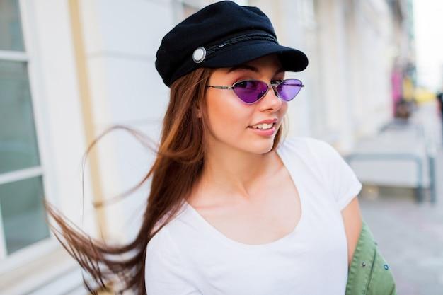 Brincalhão mulher posando ao ar livre. usando óculos retrô roxos na moda, boné preto