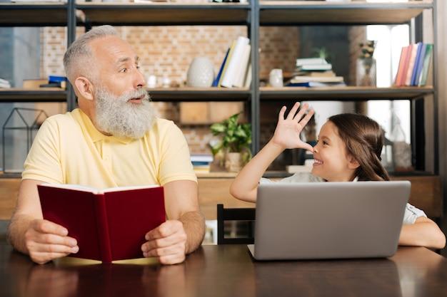 Brincando. adorável garotinha colocando o polegar no nariz e provocando o avô enquanto ele olha para ela, se surpreendendo