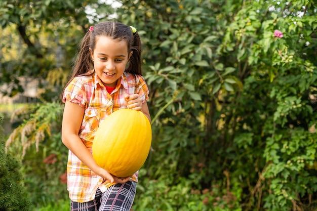 Brincando ao ar livre com uma linda garotinha segurando uma abóbora