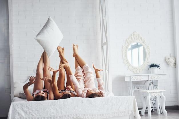 Brincando com travesseiros. felizes amigas se divertindo na festa do pijama no quarto.