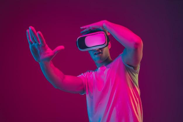 Brincando com vr, atirando, dirigindo. retrato de homem branco isolado na parede rosa-roxa do estúdio.