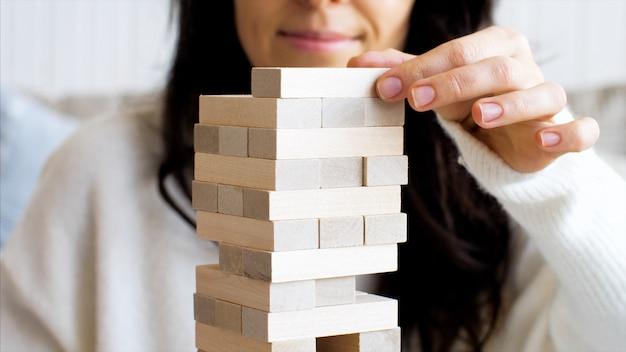 Brincando em uma torre de madeira em casa, close-up