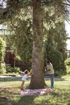 Brincando no parque. menina de cabelos cacheados brincando com o pai perto da árvore