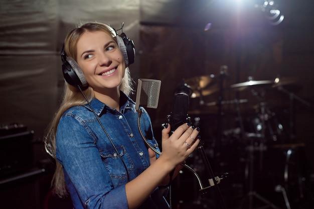 Brincar em lindo artista vocal feminino de boa aparência cantando no estúdio