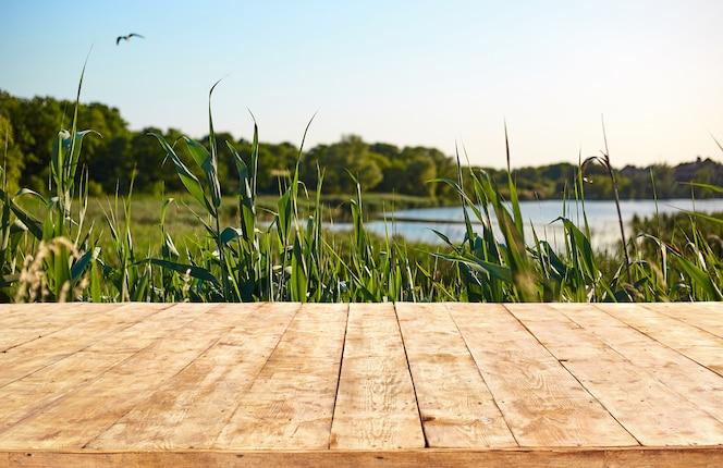 Brincar. mesa vazia de deck de madeira com fundo de folhagem bokeh.