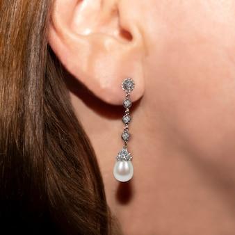 Brinco de pérola comprido na orelha de uma menina com cabelo castanho com foco seletivo