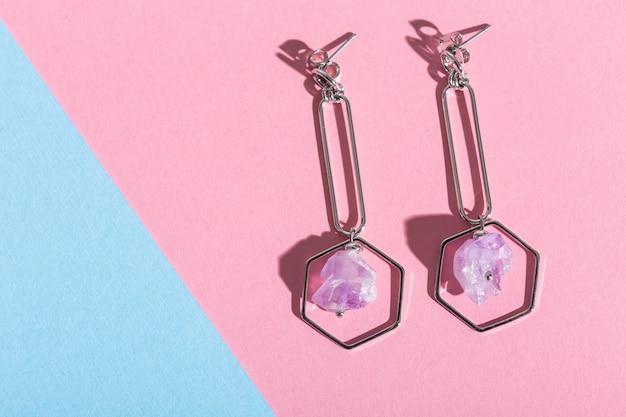 Brincos da moda na superfície rosa