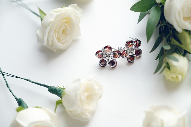 Brincos da noiva. perto de rosas brancas. parafernália de casamento e acessórios.