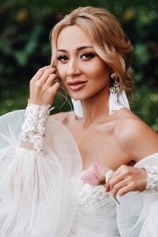 Brincos de casamento na mão feminina, ela leva os brincos, as taxas da noiva, noiva de manhã, vestido branco, use brincos.