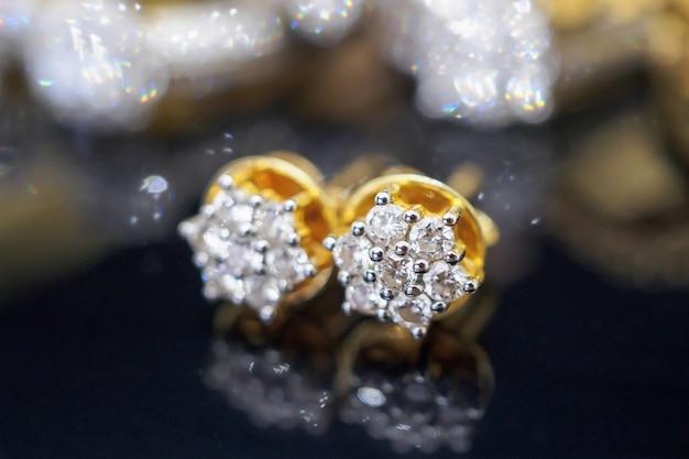 Brincos de diamante de luxo com joias de ouro com reflexo no fundo preto