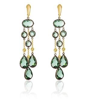 Brincos de ouro com pedras verdes em um fundo branco com reflexo