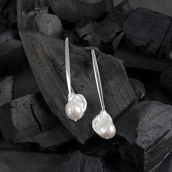 Brincos de pérola barroca branca prateada em fundo preto carvão