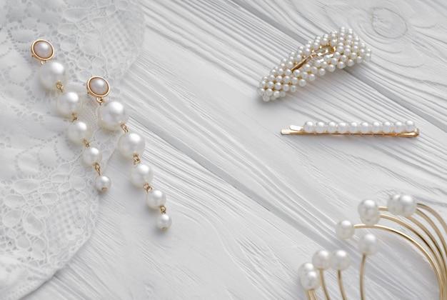 Brincos de pérola dourada, grampos de cabelo e pulseira em madeira branca