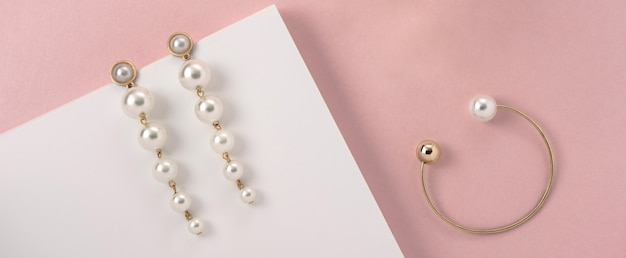 Brincos de pérola e pulseira de ouro na superfície rosa
