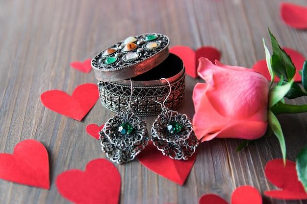 Brincos de prata com flor e corações de papel vermelho.