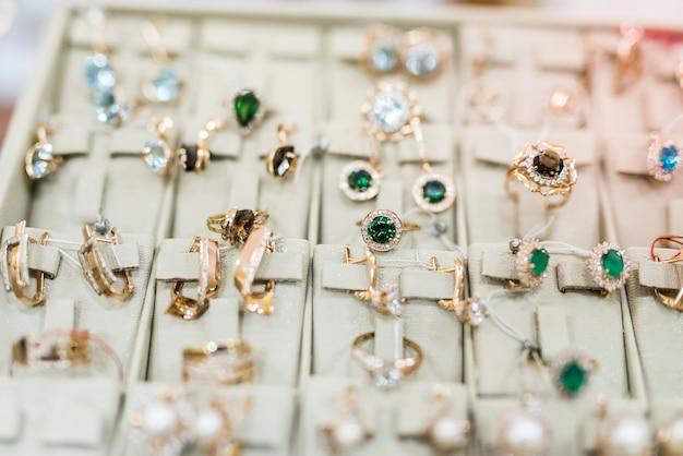 Brincos e anéis dourados em vitrine de joias