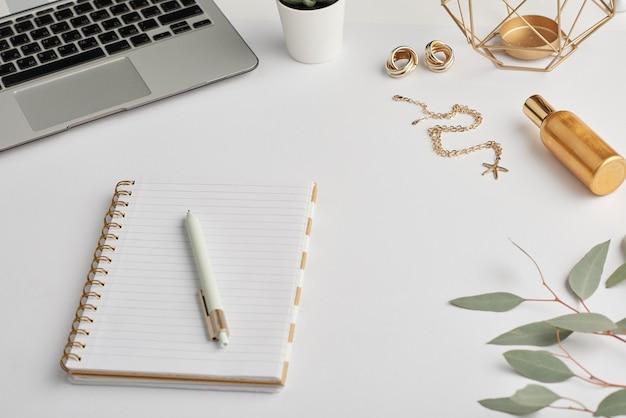 Brincos e corrente de ouro, caderno com caneta, frasco de perfume e teclado do laptop na mesa branca que é o local de trabalho do funcionário