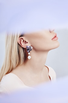 Brincos e jóias no ouvido de uma mulher loira sexy